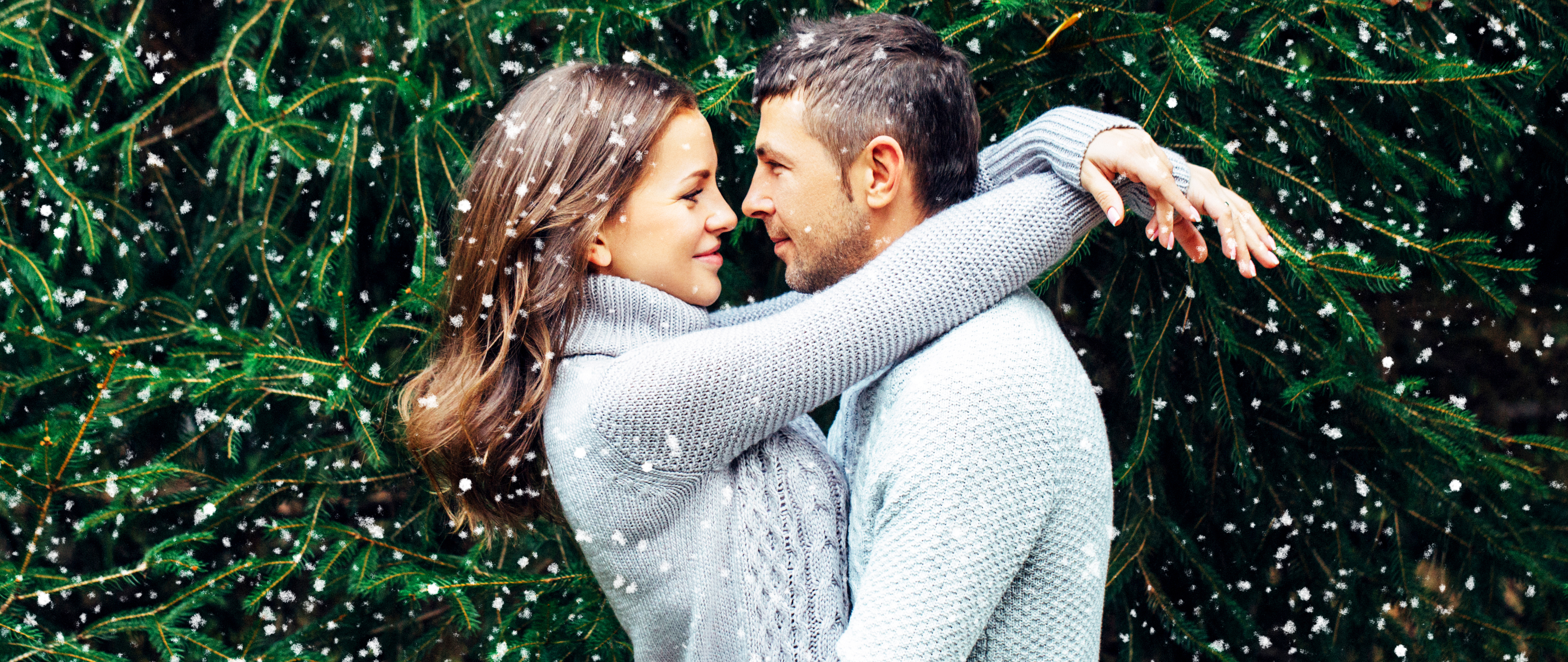 Two people in love in front of pine trees in the a light snow.